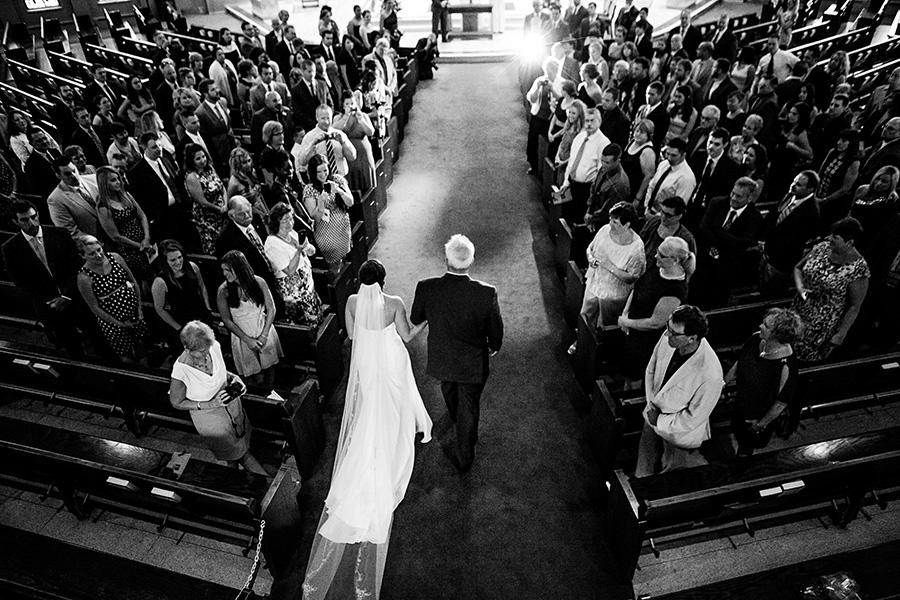 Wide photo of bride walking down the aisle with her father
