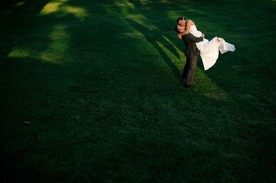 groom lifting bride up in sliver of sunlight