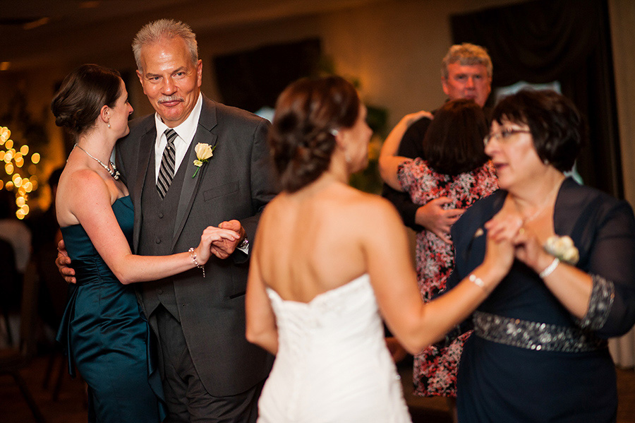 Father of the bride looking at mother and bride dancing