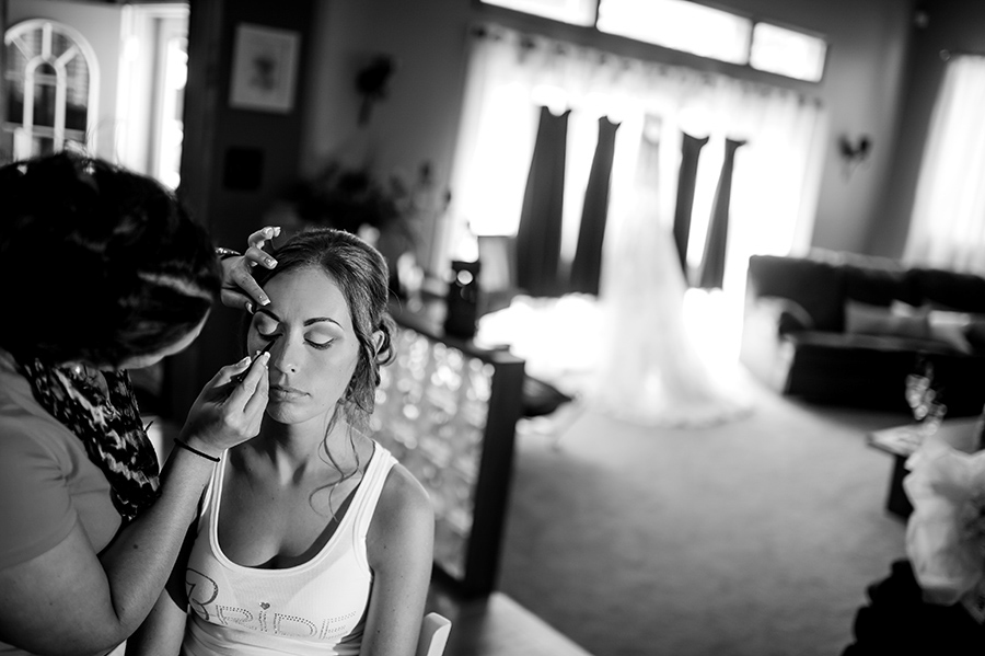 Bride getting her make up done with dresses hanging in background