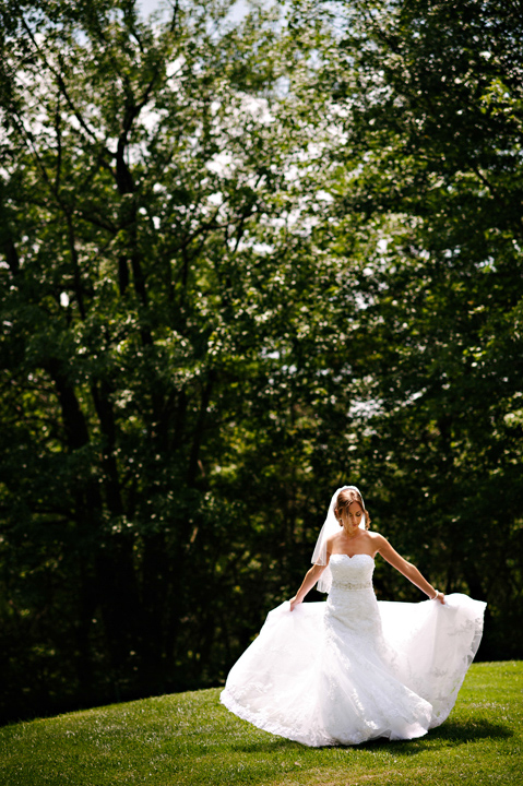 Bridal portrait of bride fixing her dress in the sun