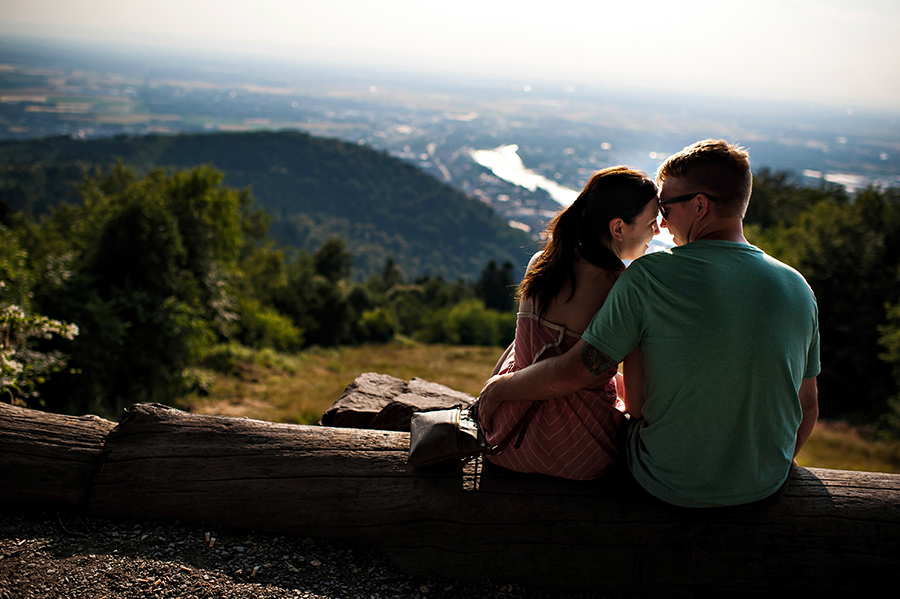 Bride and groom snuggle on a log over looking the German town of Heidelberg the day before their wedding.