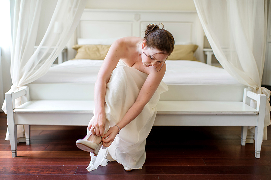 Bride sits in her wedding dress and puts shoes on before her wedding ceremony.