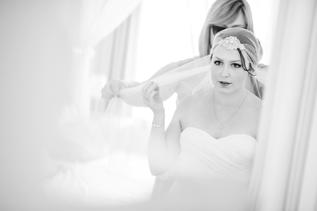 Wedding guest helps bride put her veil on.