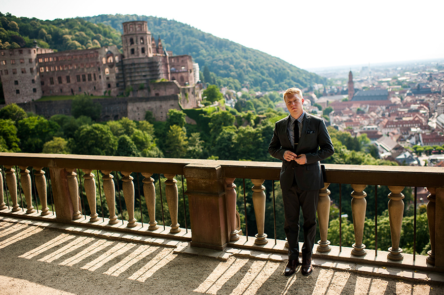 Groom fixes his jacket with Heidelberg castle in background on his wedding day