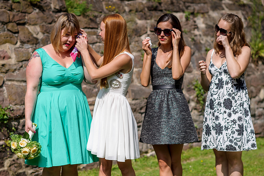 Wedding guests cry and comfort each other at emotional wedding ceremony.
