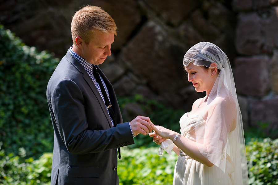 Groom places ring on brides finger during outdoor wedding ceremony.