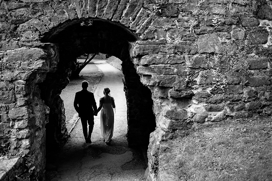Bride and groom walk through tunnel after wedding ceremony.