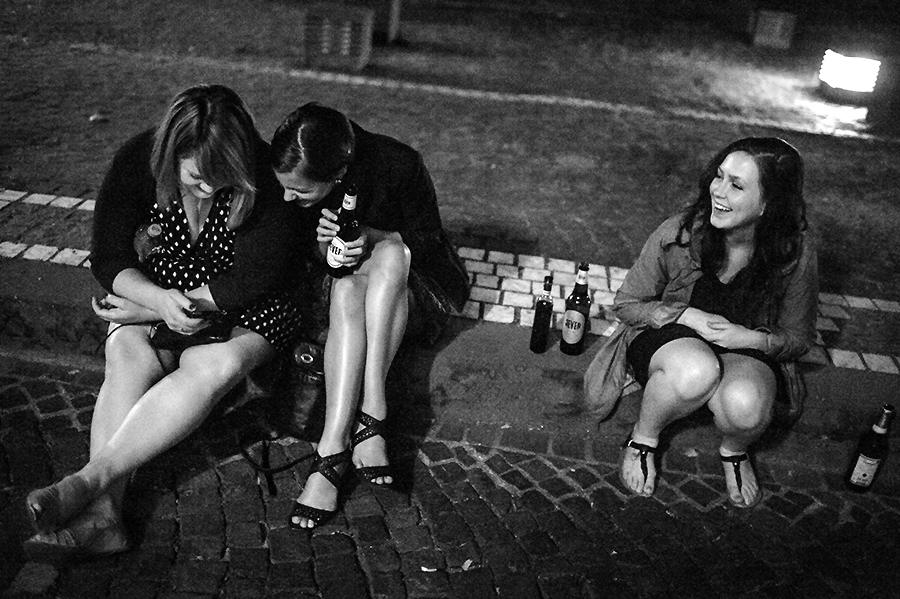 Bride and wedding guests relax on Heidelberg streets at night.