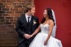 Bride and groom laughing in front of red wall at ArtsQuest SteelStacks.
