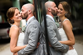 Groom kissing bride on the cheek on their wedding day.
