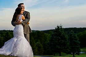 Bride and groom hugging at sunset at Woodstone Country Club.