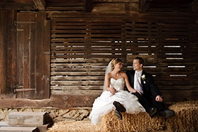 Bride and groom sitting on hay bales at the Burnside Plantation.