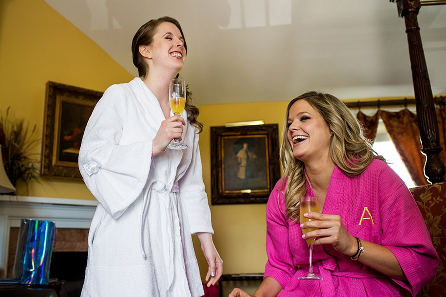 Bridesmaid and bride laughing while sipping mimosas.
