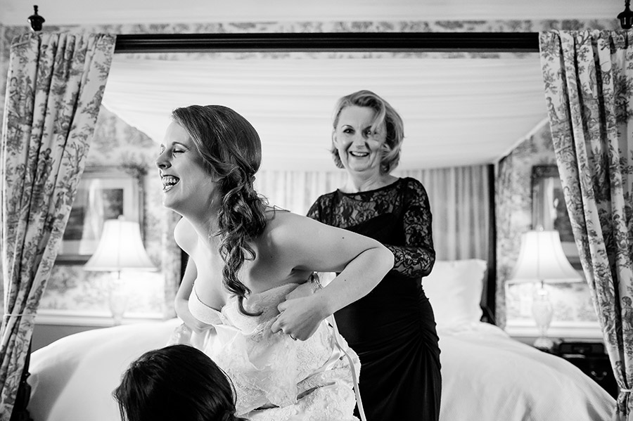 Mother of the bride and bride laughing as she gets into her wedding dress.