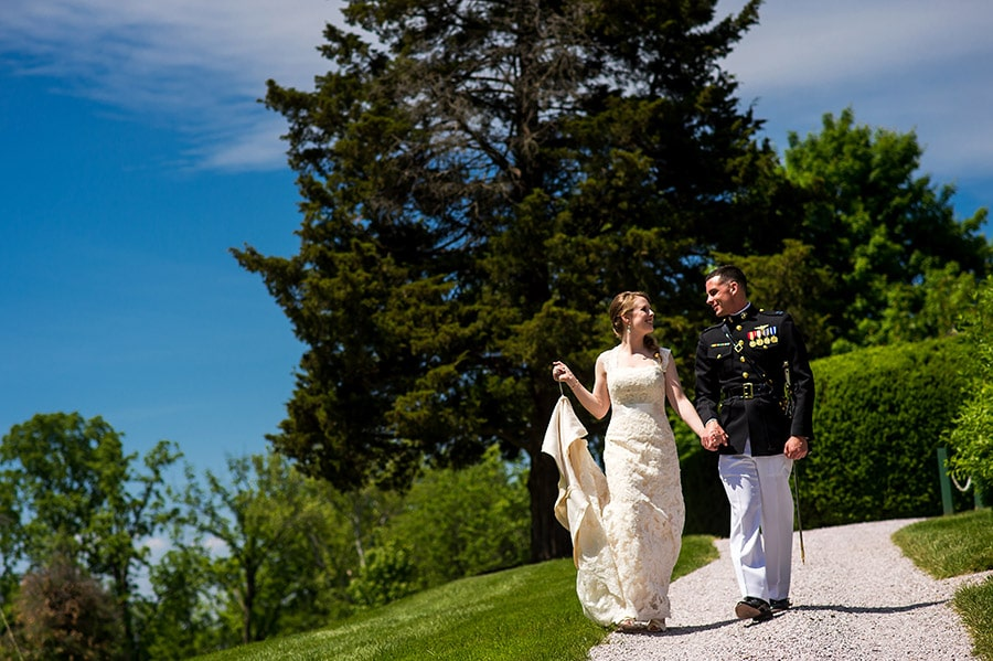Bride and groom walking together down a path.