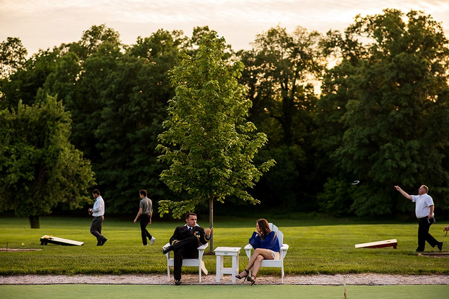 Wedding guests enjoy cocktail hour sitting on chairs and playing lawn games.