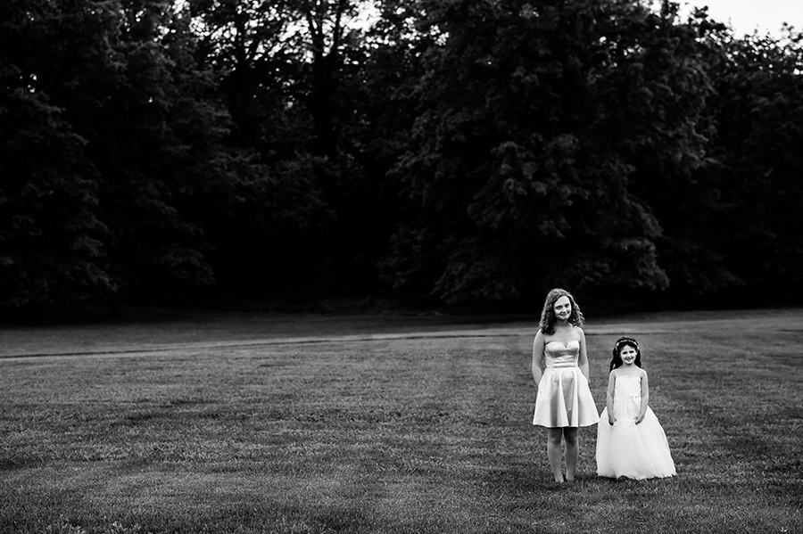 Flower girls walking through grass.