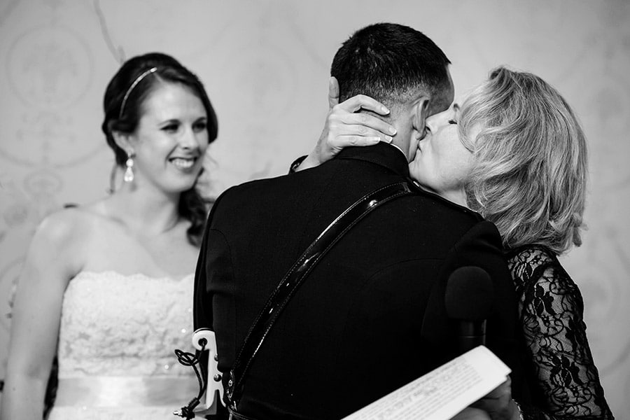 Mother of the bride kisses the groom after her speech.