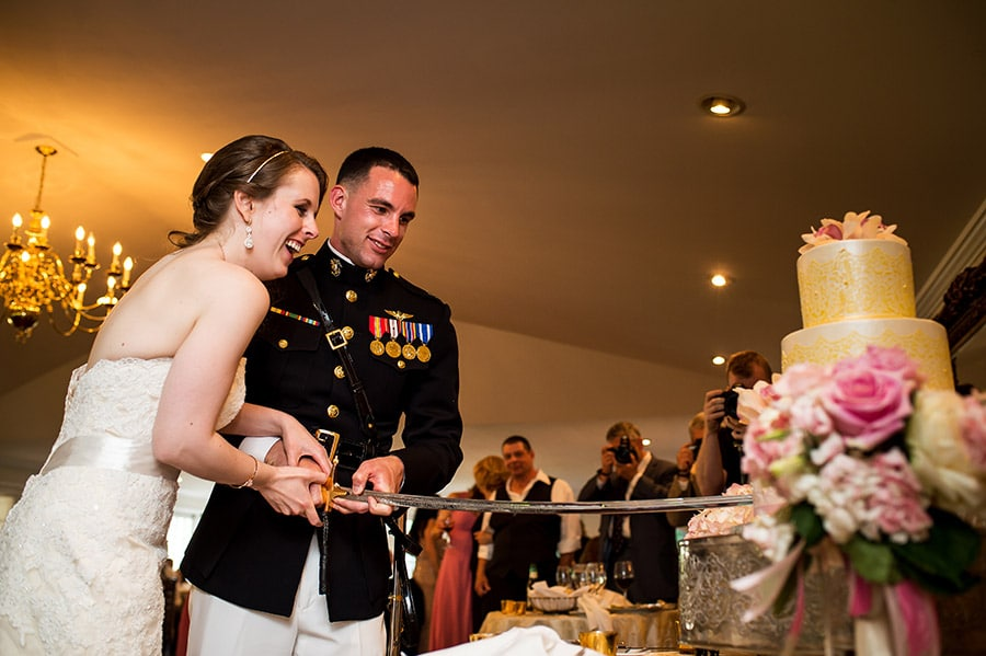 Bride and Marine groom cut the cake with Marine's NCO sword.