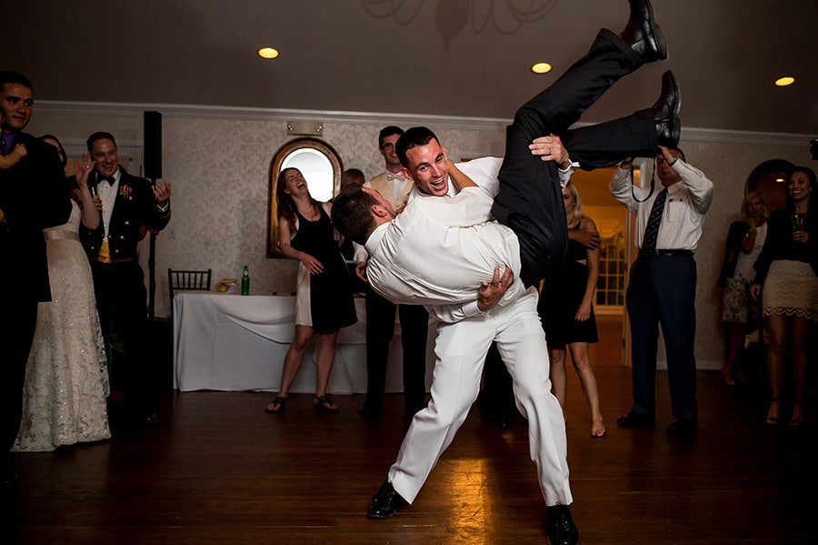 Groom dancing and carrying a wedding guests at the wedding reception.
