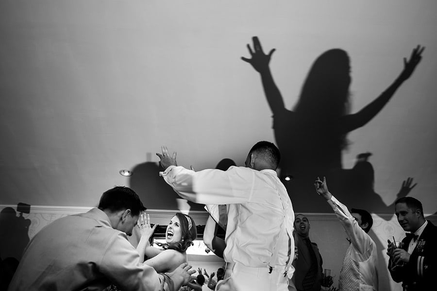 Bride dances with guests as a shadow is cast on the wall.
