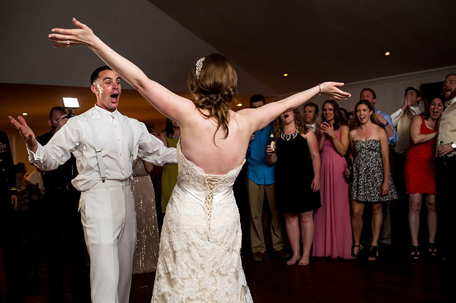 Bride and groom sing with open arms during wedding reception.