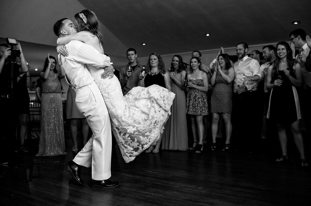 Groom lifts bride and carries her across dance floor at wedding reception.