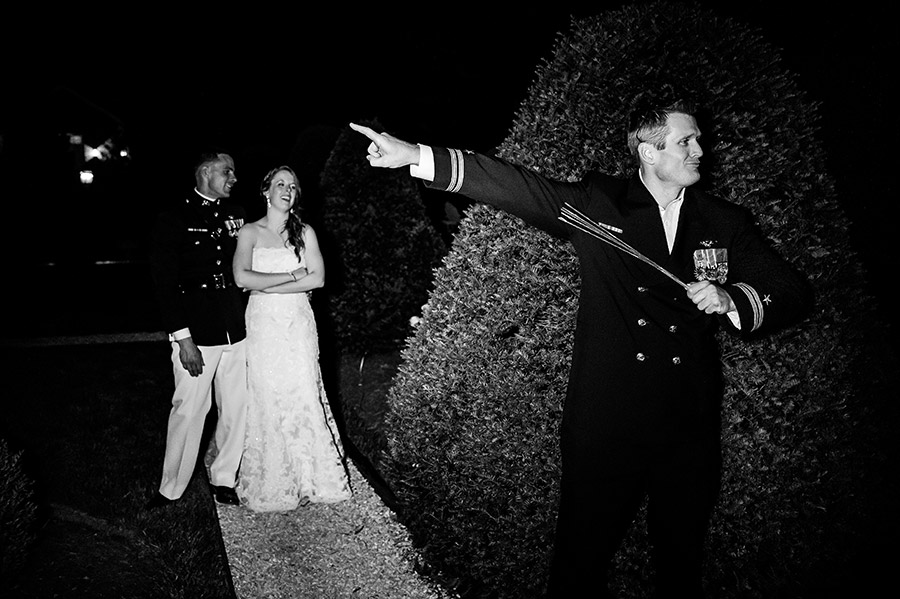 Groomsmen directs wedding guests inside as bride and groom laugh.