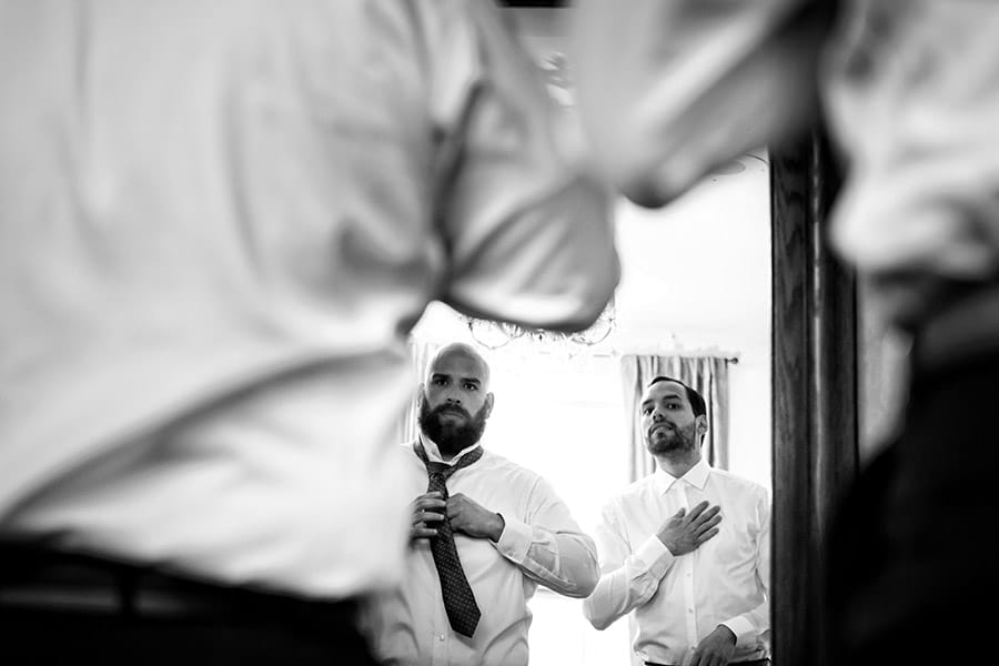 Groom and groomsmen tying their ties in the morning.