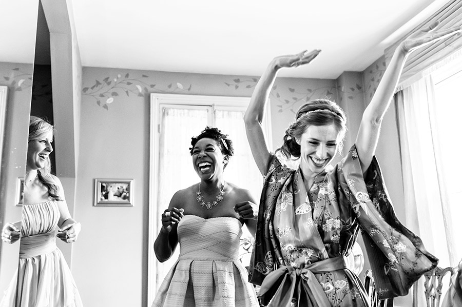 Bride and bridesmaids dancing excitedly on the wedding morning.