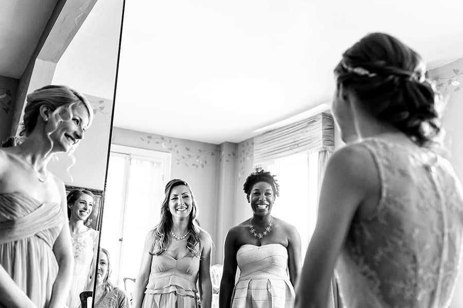 Bridesmaids reacting excitedly to bride in her dress on her wedding day.