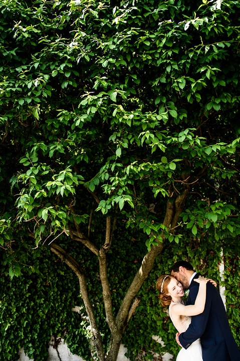 Bride and groom hugging under and tree.