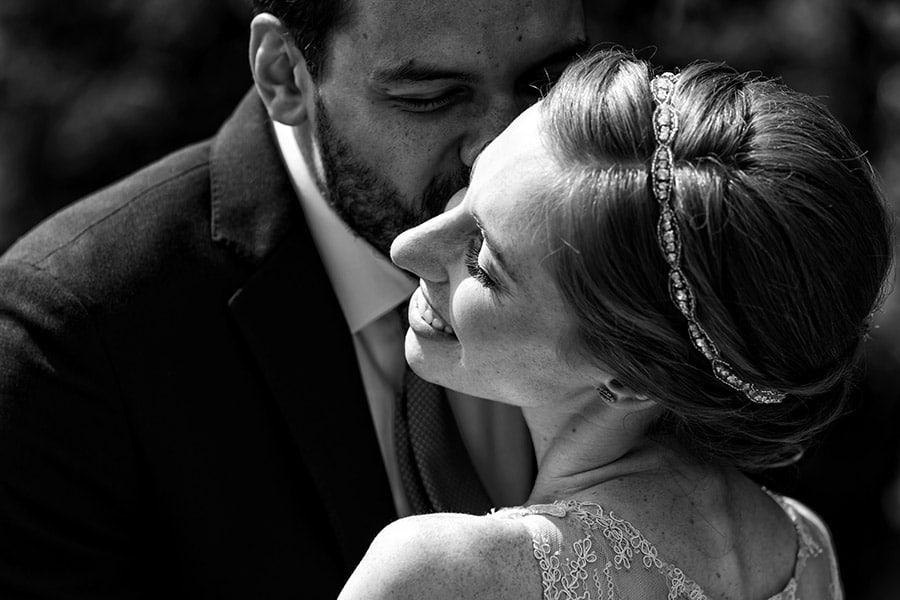 Close up of groom kissing bride's cheek.