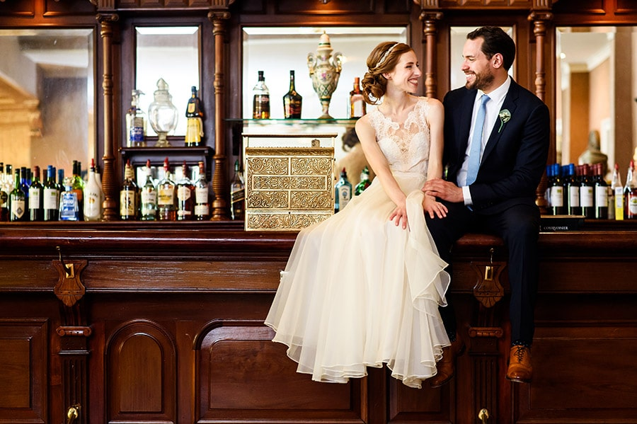 Bride and groom sitting on a bar.