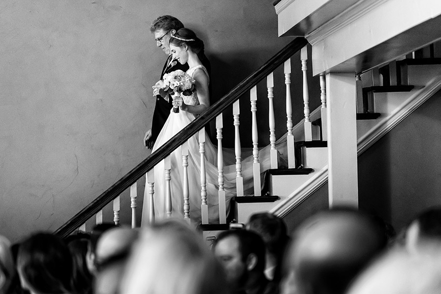 Father of the groom walking bride down the stairs to the aisle.
