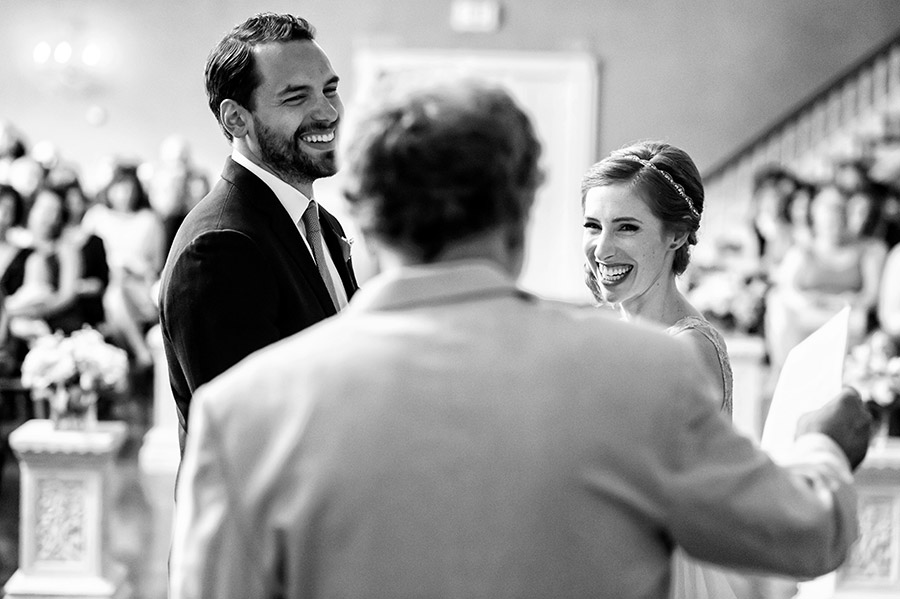 Bride and groom laughing at officiant.