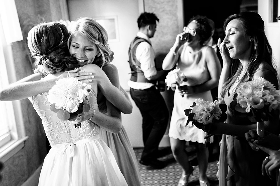 Bridesmaid hugging bride after ceremony.
