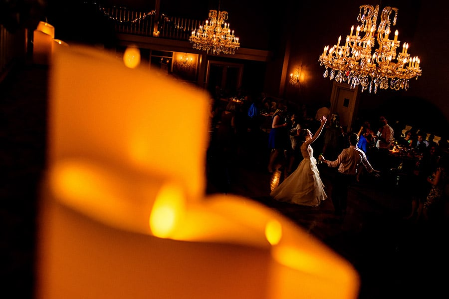 Wide shot of bride dancing on the dance floor with candles in the foreground.