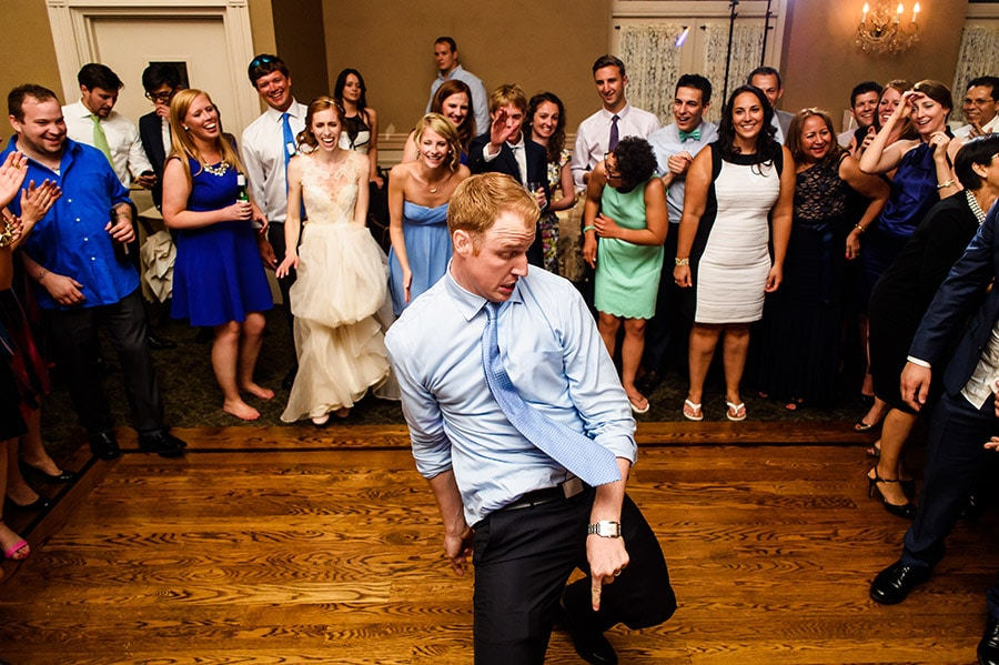 Wedding guests dancing in the middle of a group at the reception.