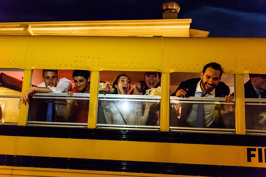 Bride, groom and guests hanging out of school bus windows.