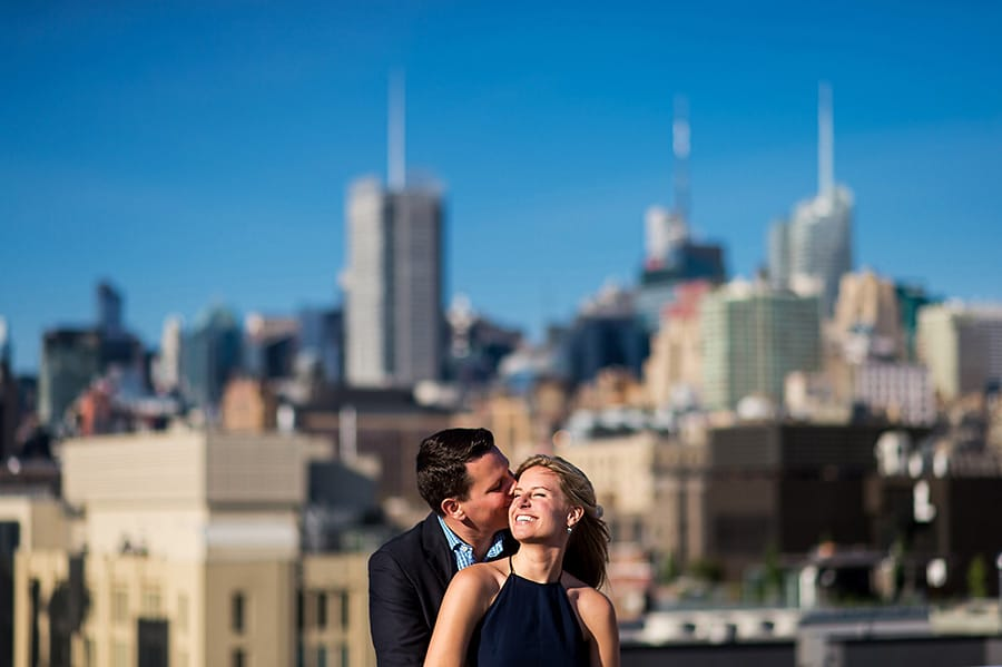 Engaged bride-to-be smiling as groom to be kisses her on the cheek with NYC skyline in background.
