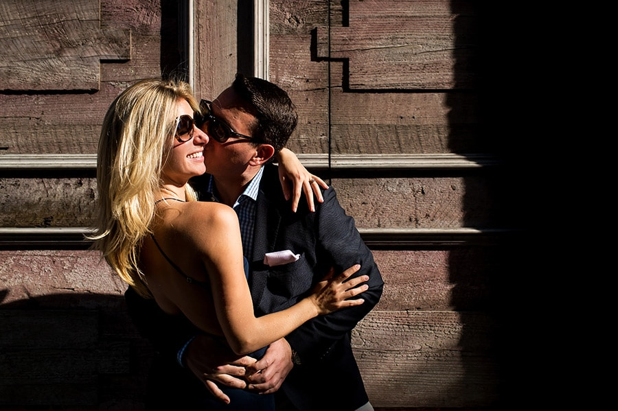 Groom to be kissing his bride to be on the cheek in the sunlight!