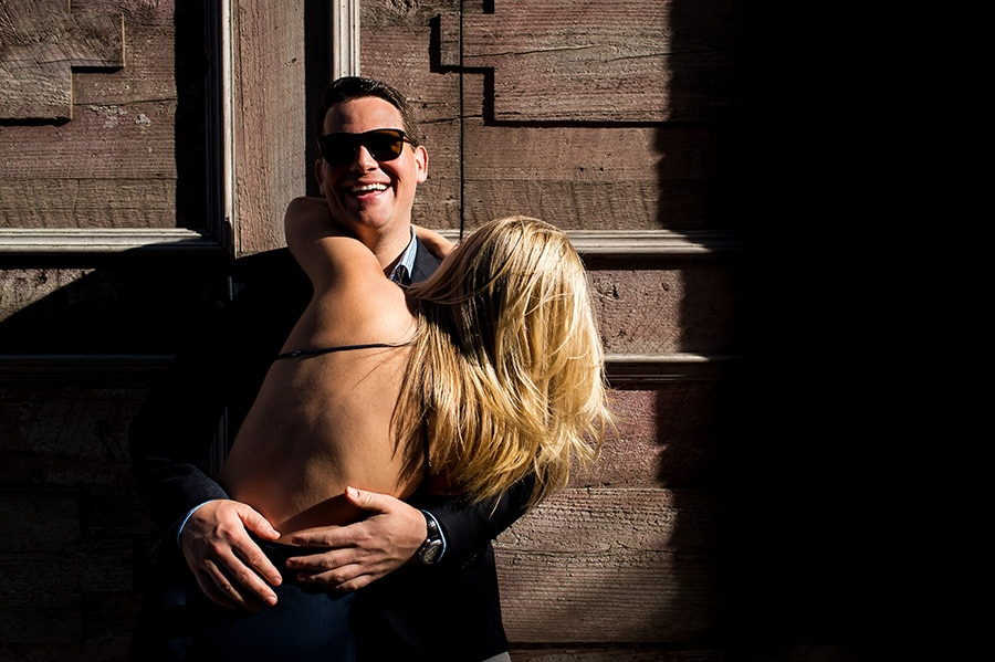 Bride-to-be laughing and hugging her groom-to-be during their engagement session in NYC.