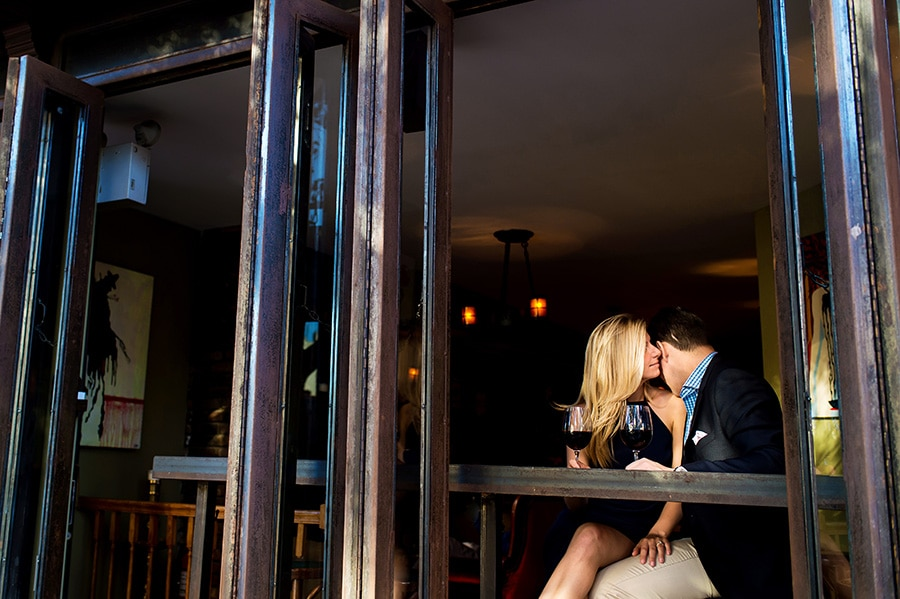 Groom-to-be kisses his bride-to-be on her shoulder in an NYC wine bar.