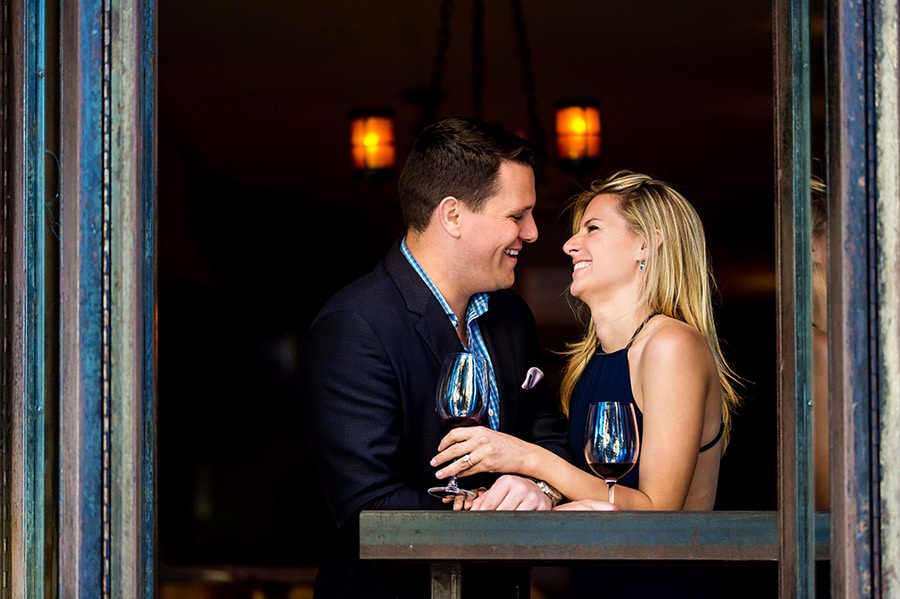 Engaged couple laughing while sipping wine in an