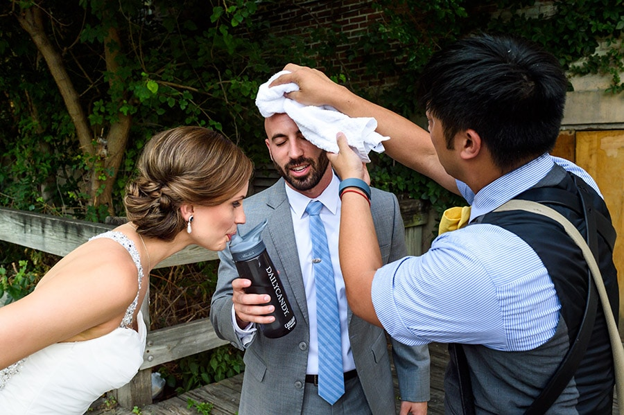 Philadelphia Wedding Photographer wiping grooms sweat as bride drinks water.