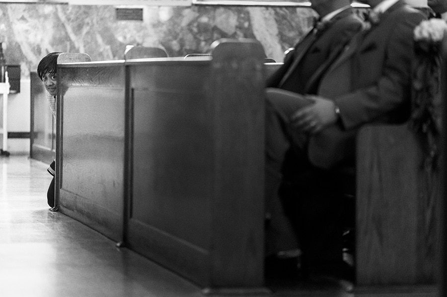 photographer peeking around pew in church.