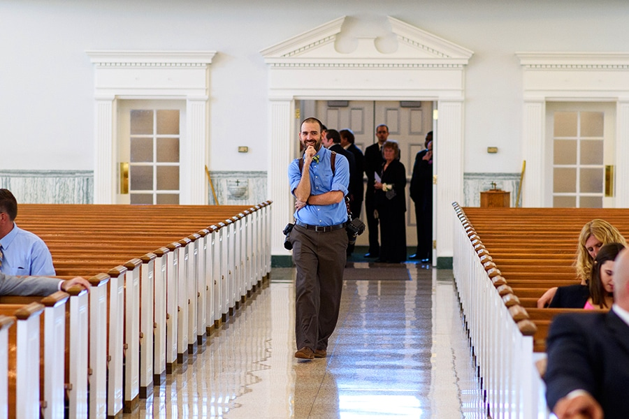 Photographer doing test shot walking down aisle in church on wedding day.