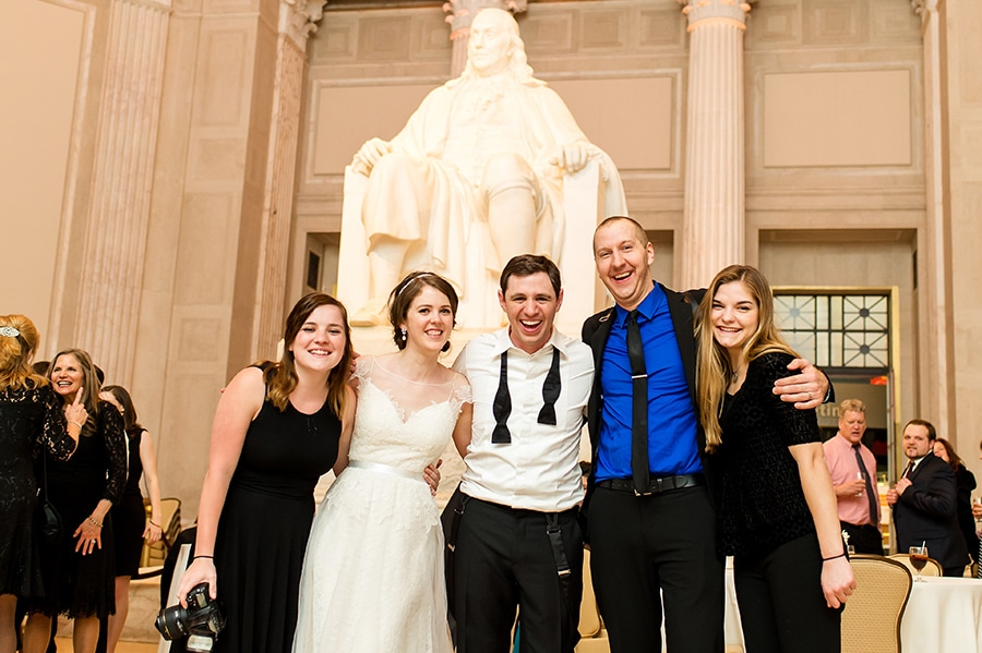 Philadelphia photographer poses with bride and groom at Franklin Institute on their wedding day.